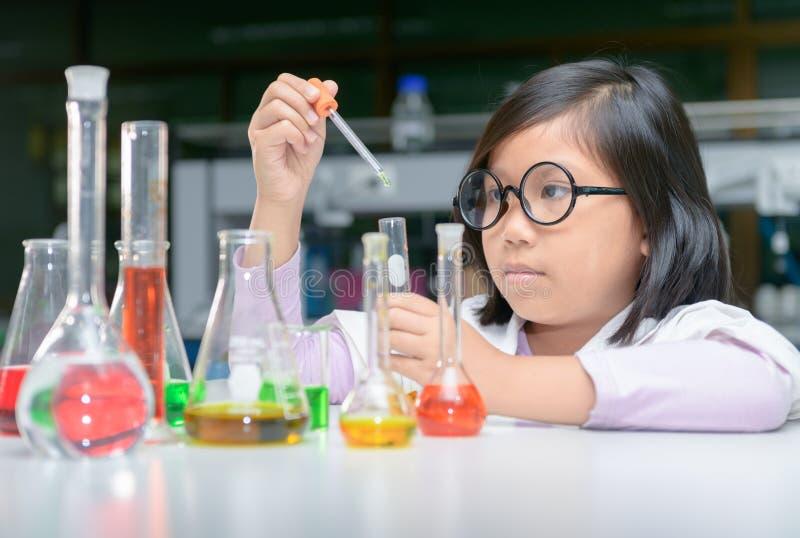 Kleiner Wissenschaftler, der Experiment mit Reagenzglas macht lizenzfreies stockbild