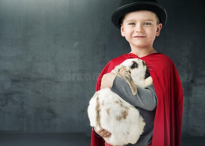 Kleiner Zauberkünstler, der ein magisches Kaninchen hält stockfotografie