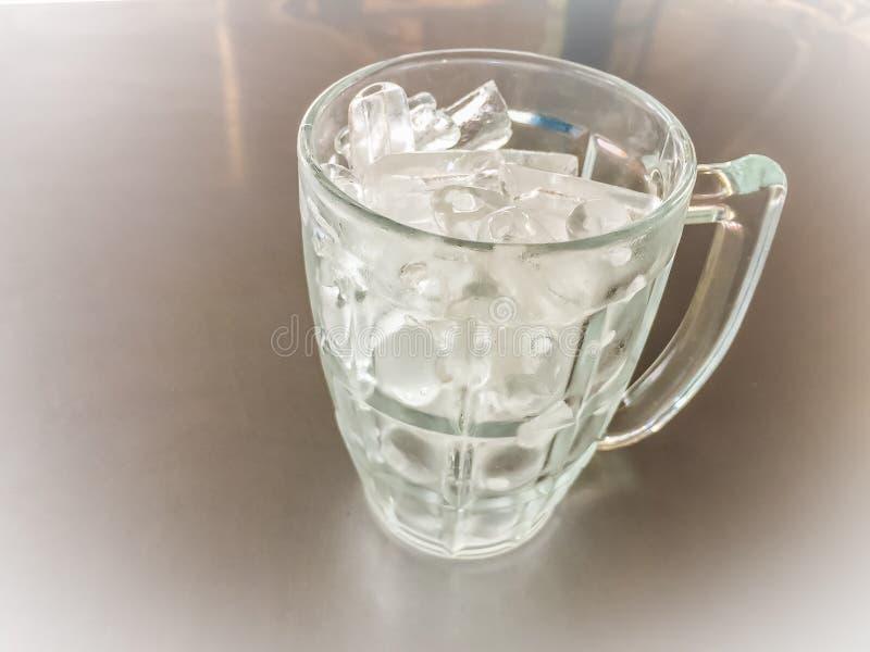Kleiner Zylinder formte vom Eis im Glaskrug, der auf den Stahl t gesetzt wurde stockfotografie