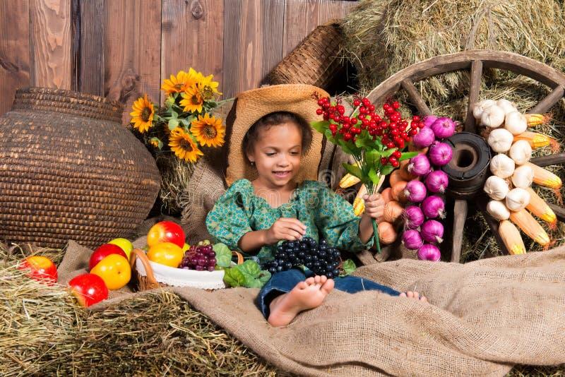 Kleines afrikanisches Mädchen im Cowboyhut, der auf Strohtasche mit Früchten sitzt lizenzfreie stockfotografie