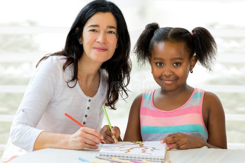 Kleines afrikanisches Mädchen und Lehrer, die zusammen zeichnet lizenzfreies stockbild