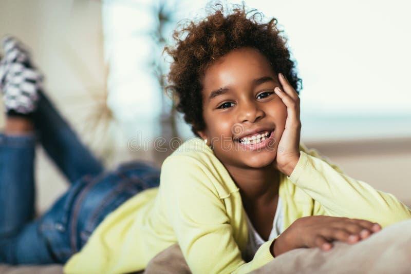 Kleines Afroamerikanermädchen, das Kamera, lächelndes Mischrassekind zu Hause aufwirft für Porträt betrachtet lizenzfreie stockbilder