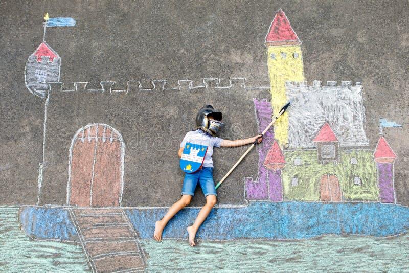 Kleines aktives Kinderjungenzeichnungsritterschloss und -festung mit bunten Kreiden auf Asphalt Glückliches Kind im Sturzhelm und lizenzfreie stockfotografie
