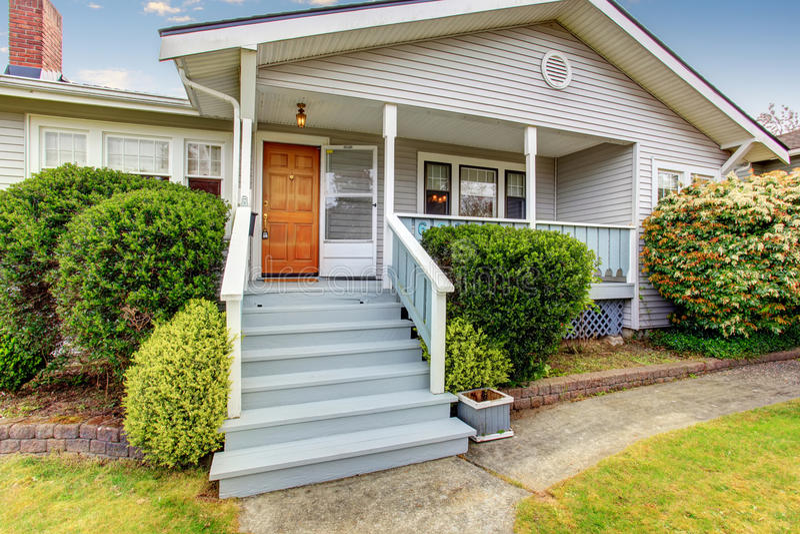 Kleines amerikanisches Haus mit dem Licht außen und weißer Ordnung stockfotografie