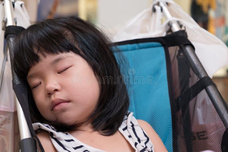 Kleines asiatisches Baby, das in einem Spaziergänger schläft stockbild