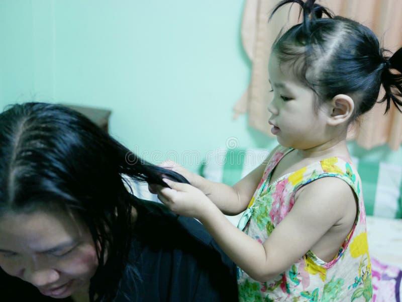 Kleines asiatisches Baby, das ihr Tante ` s Haare getan gibt stockbild
