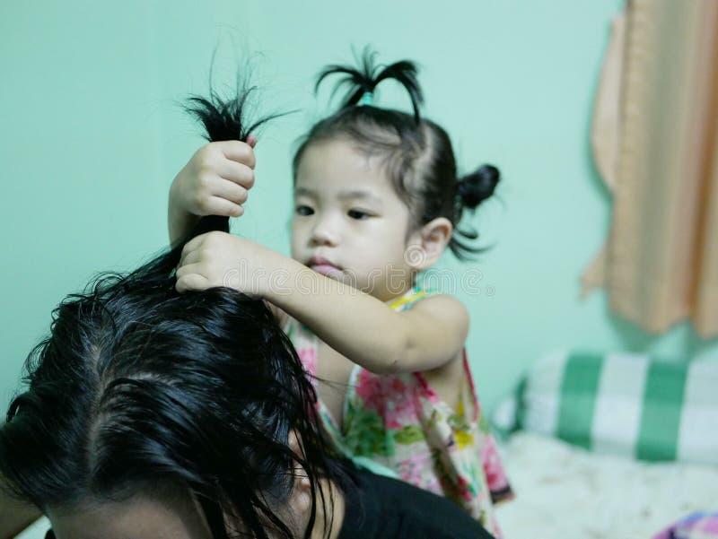 Kleines asiatisches Baby, das ihr Tante ` s Haare getan gibt lizenzfreie stockbilder