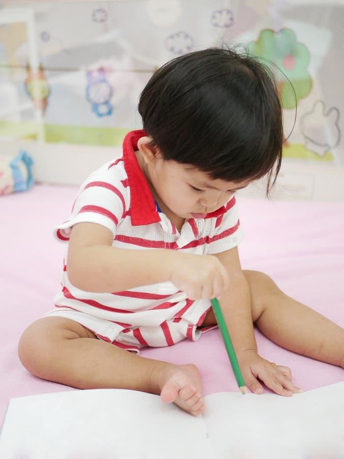 Kleines asiatisches Baby, das lernt, einen Bleistift zu halten und auf ein Buch zeichnet lizenzfreies stockbild