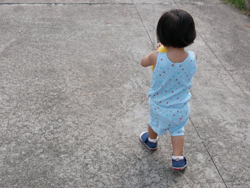 Kleines asiatisches Baby, das lernt und, das übt, durch zu gehen stockfotografie