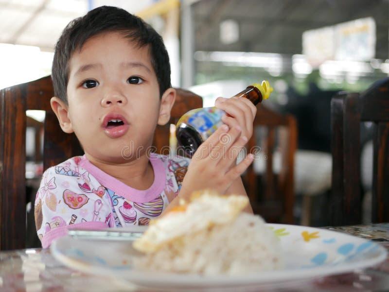 Kleines asiatisches Baby, das Sojabohnenölbohnensoße auf Reis mit Spiegelei durch hinzufügt lizenzfreies stockfoto