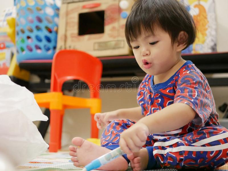 Kleines asiatisches Baby genießt, unter Verwendung des großen Farbstiftes zu malen stockfotografie