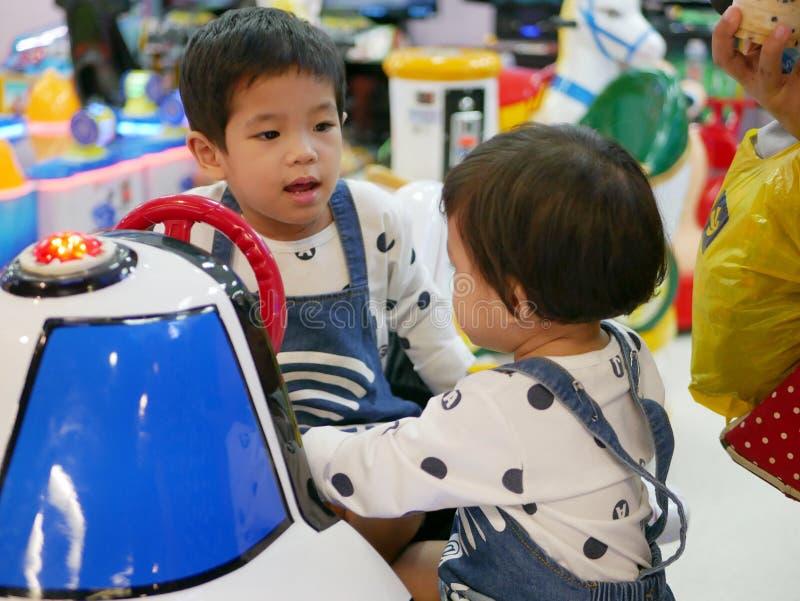 Kleines asiatisches Baby lehnt ab, ihr kleines Schwesterchen ein Arcade-Spiel zusammen spielen zu lassen lizenzfreie stockfotos