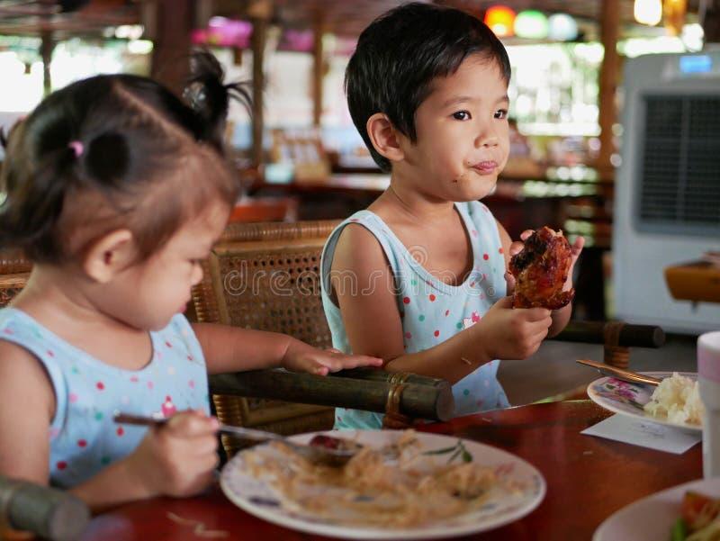Kleines asiatisches Babyrecht, das einen gegrillten Hühnertrommelstock lernt, ihn durch zu essen hält stockfotografie