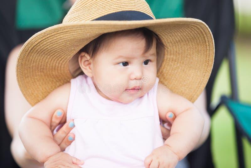 Kleines asiatisches Kind, das einen großen Strohhut trägt und auf ihrem Mutter ` s Schoss sitzt lizenzfreie stockfotografie