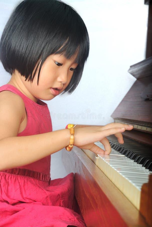 Kleines asiatisches Kind, welches das Klavier spielt lizenzfreie stockfotografie
