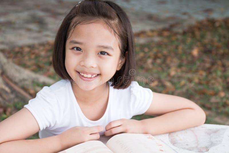 Kleines asiatisches Kinderlächeln und Ablesen eines Buches lizenzfreie stockfotos