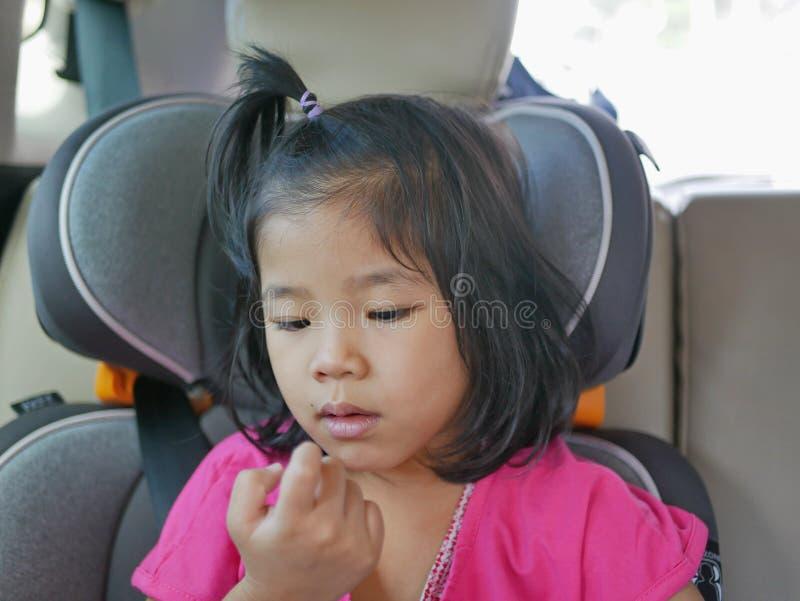 Kleines asiatisches Mädchen, das nach dem Nasen-Pflücken ihre eigenen Booger anschaut - Kindergewohnheit / Verhalten lizenzfreies stockbild