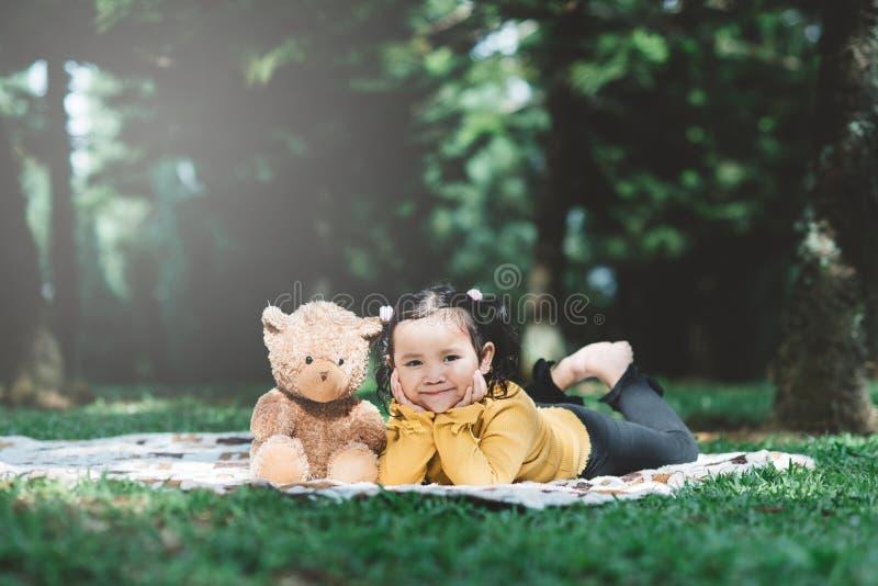 Kleines asiatisches Mädchen, das neben ihrem Teddybär liegt stockbild
