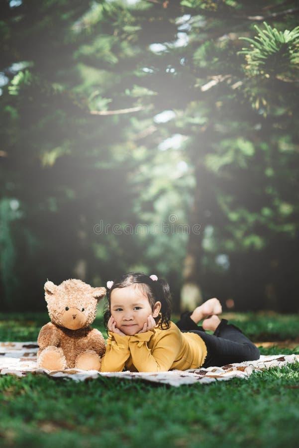 Kleines asiatisches Mädchen, das neben ihrem Teddybär liegt stockfotos