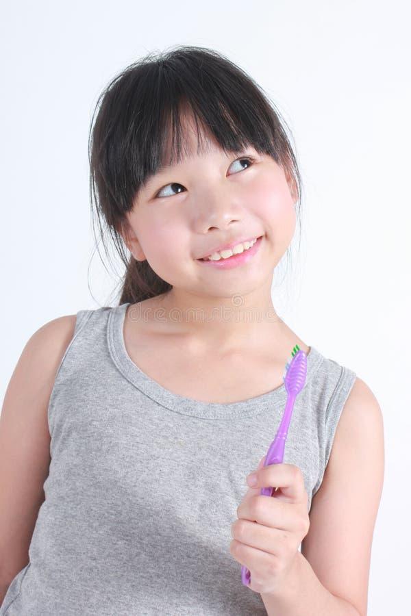 Kleines asiatisches Mädchen, das Zahnpasta hält stockbild