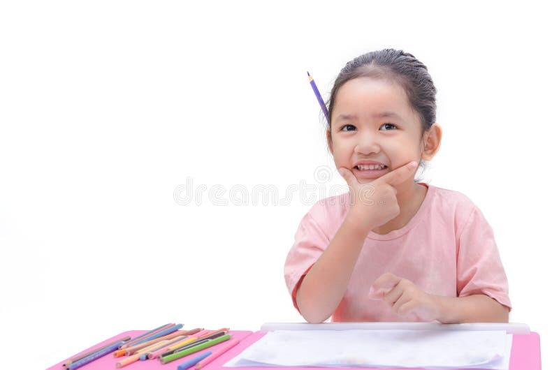 Kleines asiatisches Mädchen des Lächelns mit Bleistiftfarbe lokalisiert auf Weißrückseite stockfotos