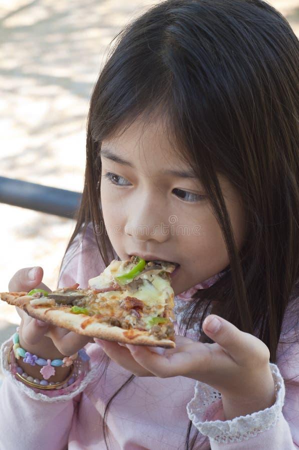 Kleines asiatisches Mädchen genießen Pizza. stockfoto