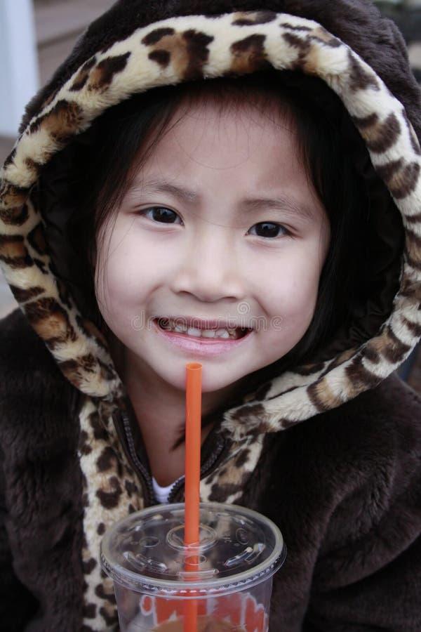 Kleines asiatisches Mädchen mit dem Haubentrinken stockbilder