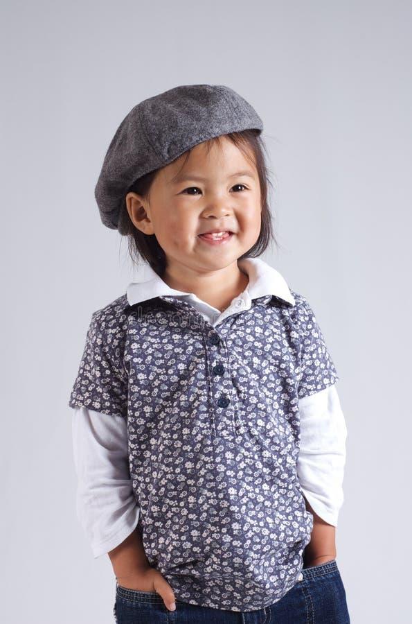 Kleines asiatisches Mädchen mit einem Hut lizenzfreie stockbilder