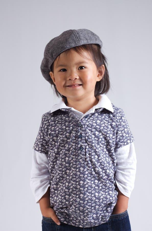 Kleines asiatisches Mädchen mit einem Hut lizenzfreies stockfoto