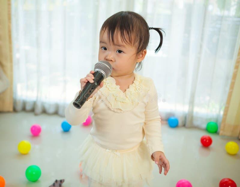 Kleines asiatisches Mädchen mit Mikrofon lizenzfreies stockbild