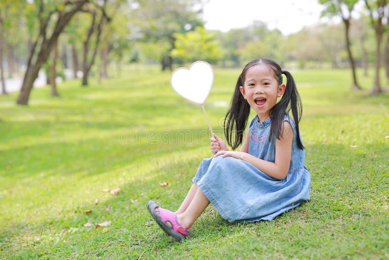 Kleines asiatisches Mädchen Smilling, das den leeren Herzaufkleber liegt auf grünem Gras am Sommergarten hält lizenzfreie stockfotografie