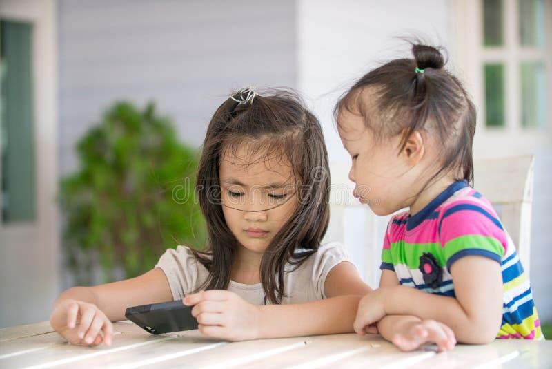 Kleines asiatisches Mädchen zwei, das auf Stuhl unter Verwendung des Handys sitzt lizenzfreie stockbilder