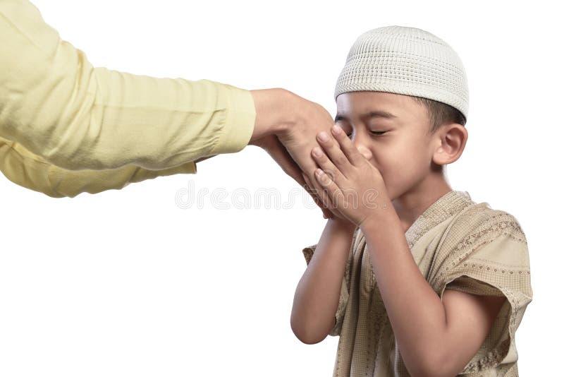 Kleines asiatisches moslemisches Kind in küssender Elternhand der weißen Kappe stockfotografie