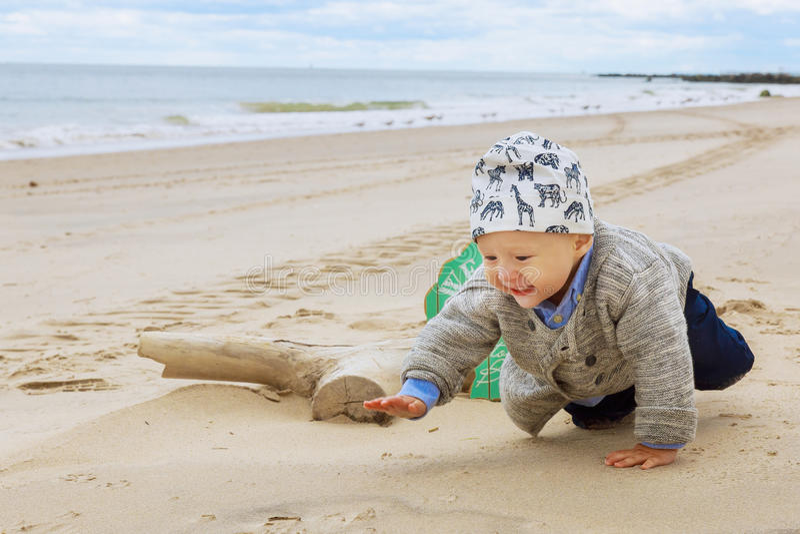 Kleines Baby auf dem Strand, spielend lizenzfreies stockfoto
