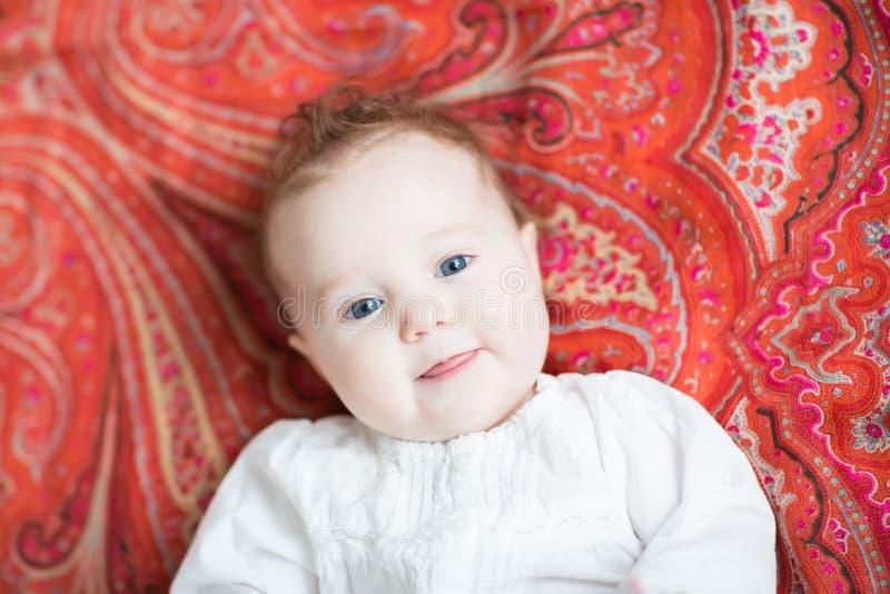 Kleines Baby auf einem bunten roten Tulpenmotivschal lizenzfreies stockfoto