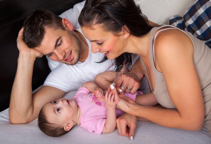 Kleines Baby, das auf dem Bett mit seinen Eltern liegt stockfotos