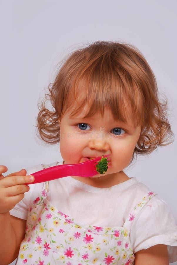 Kleines Baby, das Brokkoli mit Gabel isst lizenzfreies stockfoto