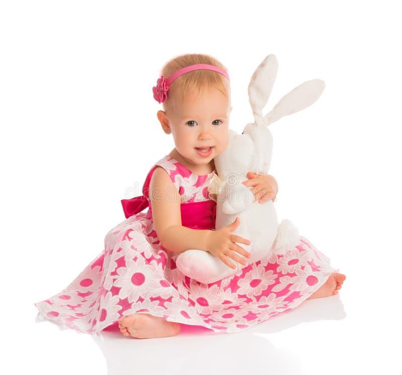 Kleines Baby, das ein Spielzeughäschen auf Weiß umarmt stockfotos