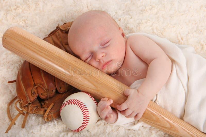 Kleines Baby, das einen Baseballschläger anhält stockbilder