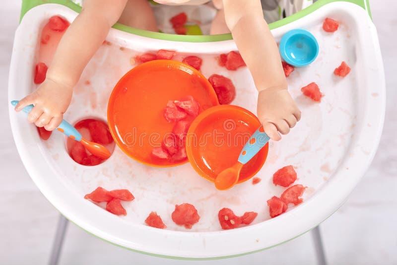 Kleines Baby, das Löffel und Gabel hält und Verwirrung auf Tabelle macht stockbild