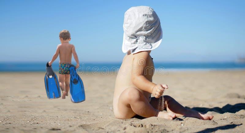 Kleines Baby, das mit dem Sand sitzt und spielt Lustiger netter ch stockfotografie