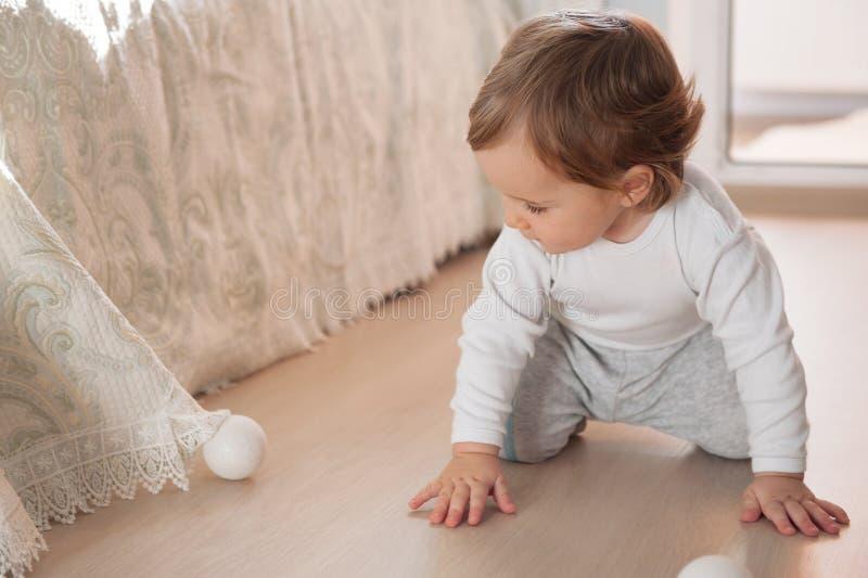 Kleines Baby, das mit silbernen Weihnachtsbällen spielt lizenzfreies stockbild