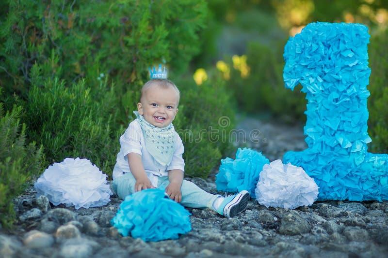 Kleines Baby, das nah an Nummer Eins-Geburtstagszahl-Blaufarbe sitzt stockbild