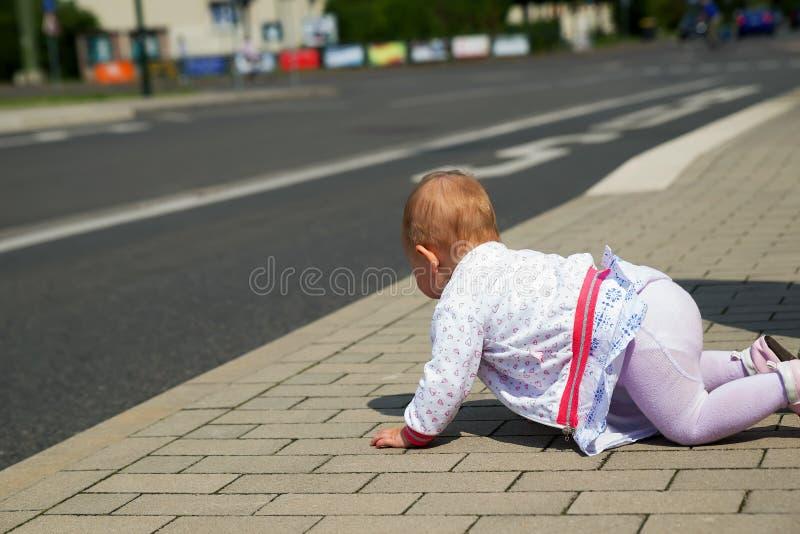 Kleines Baby in der weißen Kleidung, die entlang die Straße kriecht stockfoto