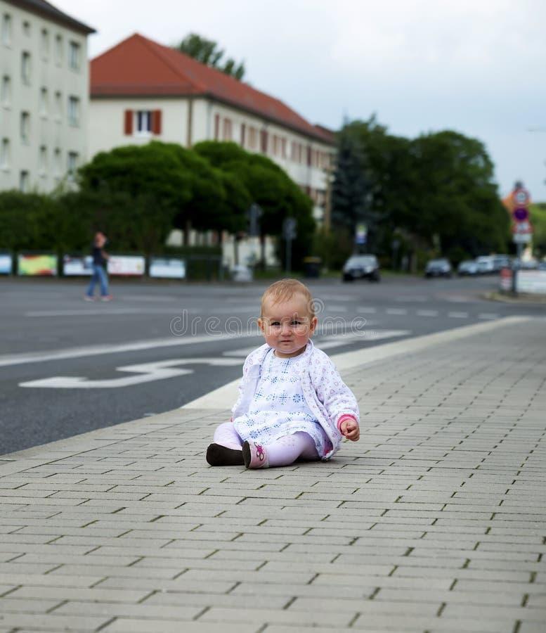 Kleines Baby in der weißen Kleidung, die entlang die Straße kriecht lizenzfreie stockbilder