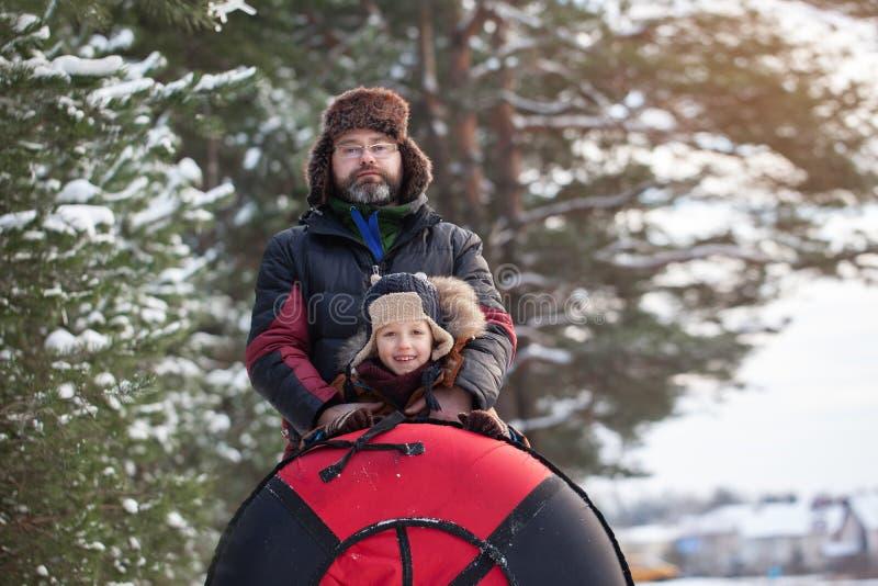 Kleines Baby des Porträts und sein Vater mit Rohr am Wintertag Spaß im Freien für Familie Weihnachtsferien stockbilder