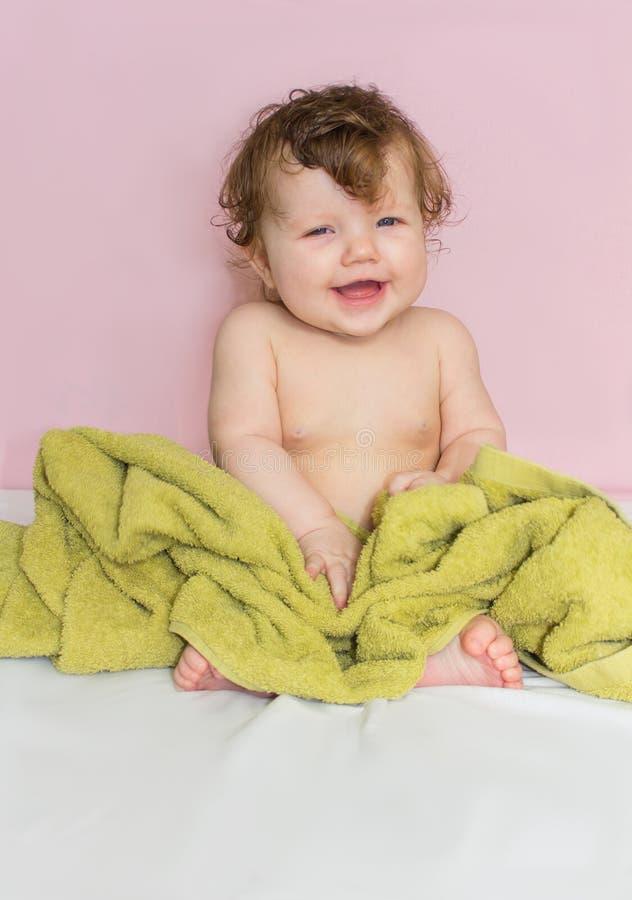 Kleines Baby in einem grünen Tuch nach dem Baden stockfoto