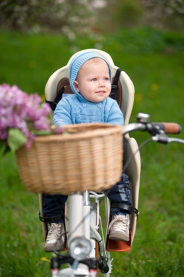 Kleines Baby mit einer Haube, die im Fahrradstuhl sitzt stockbilder