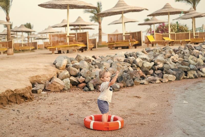 Kleines Baby mit entzückendem Gesicht mit Rettungsgürtel auf Strand stockfotos