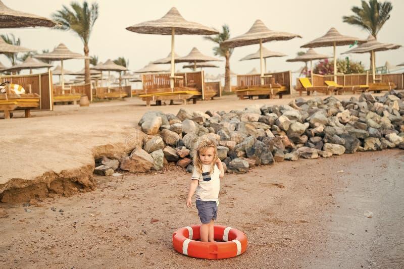 Kleines Baby mit entzückendem Gesicht mit Rettungsgürtel auf Strand stockbilder
